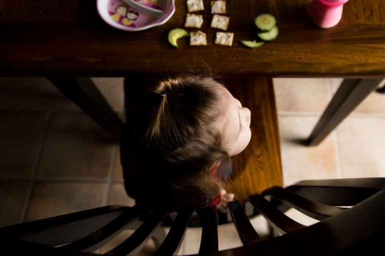 portrait of a toddler from above, warm tones, toddler eating lunch, a toddler on a chair from above
