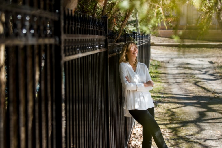 Woman laughing in dappled light along a wrought iron fence