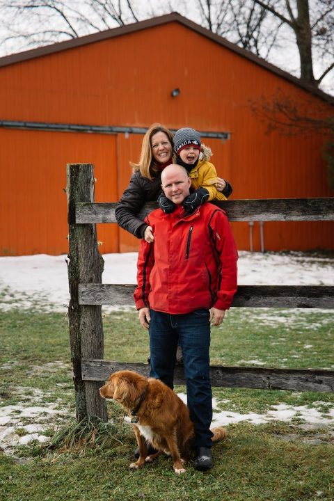 Family portrait in the snow with their dog