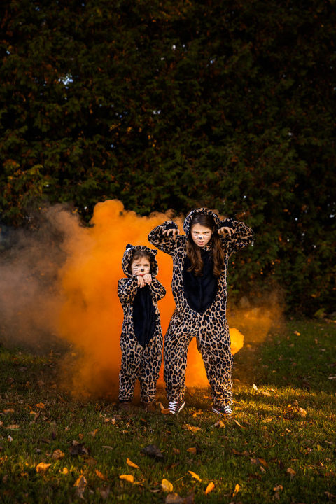 Halloween image of kids dressed up in front of an orange smoke bomb
