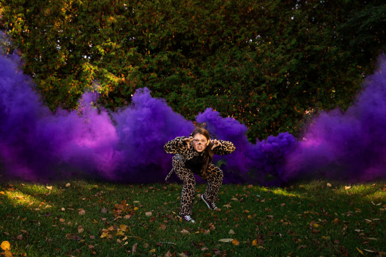 Halloween image of kid dressed up in front of a purple smoke bomb