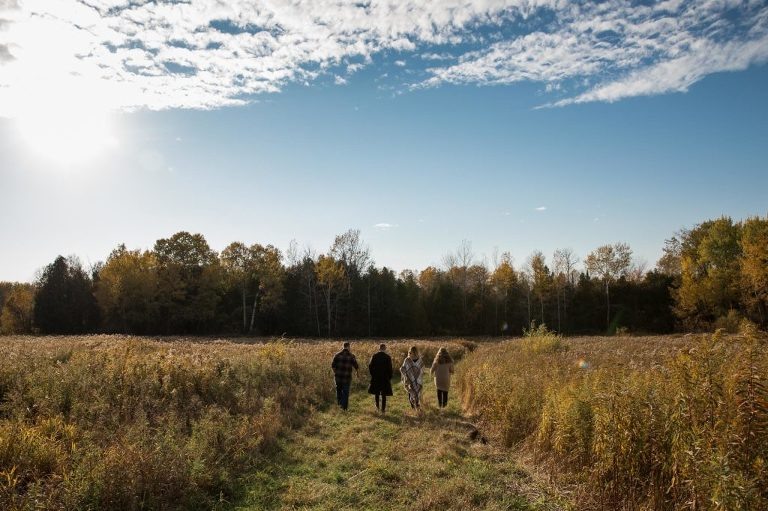 Adult kids walking in a field during the fall with beautiful blue sky