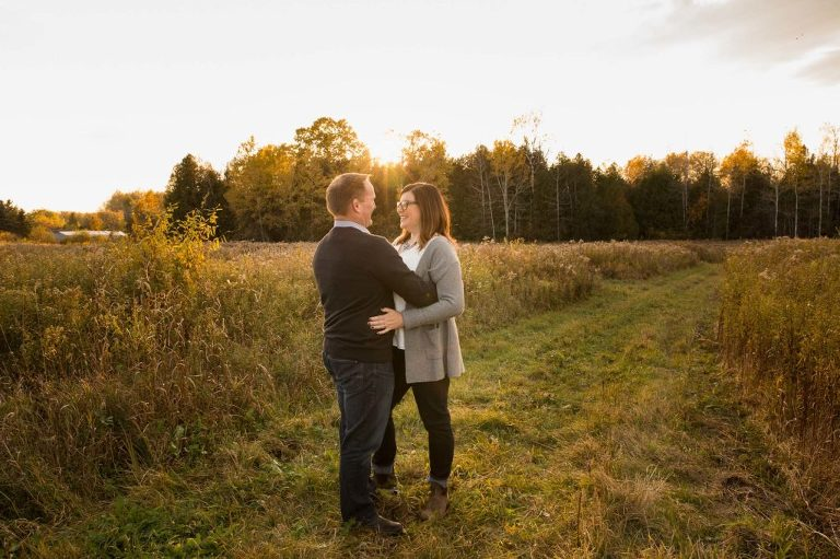 A romantic couple in an embrace in a golden field at sunset. Emotive storytelling images