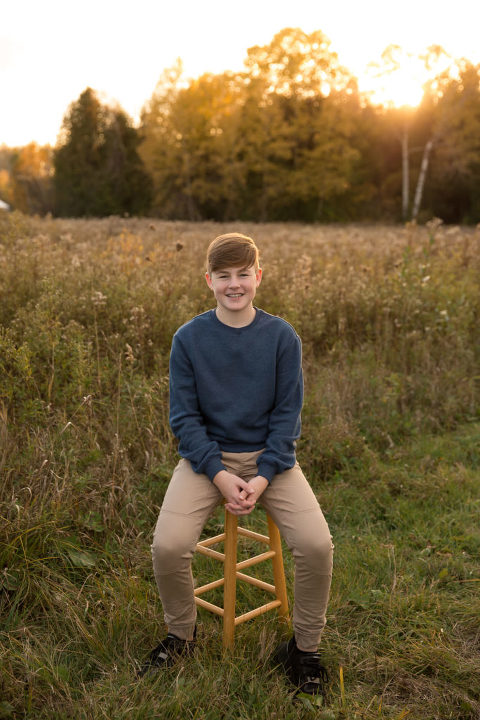 Young man sitting in a field at golden hour